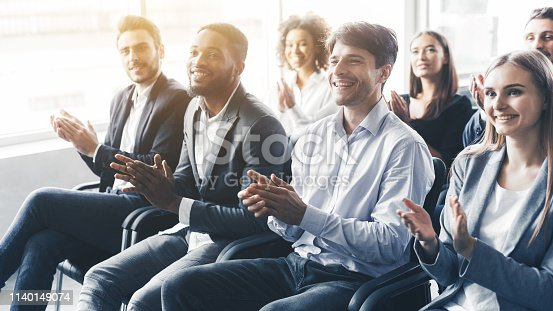 1180918029 istock photo Applauding to speaker. Group of happy business people in conference hall 1140149074