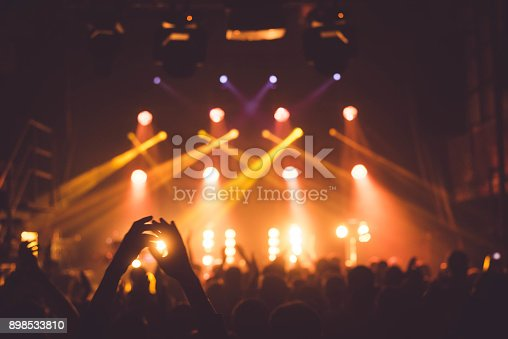 istock applause and raised hands at concert. Nightclub life 898533810