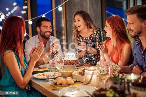 Friends having dinner party at home. Celebrating birthday party for their friend. They are happy and well dressed. Home is decorated with festive string lights and candles. Evening or night.