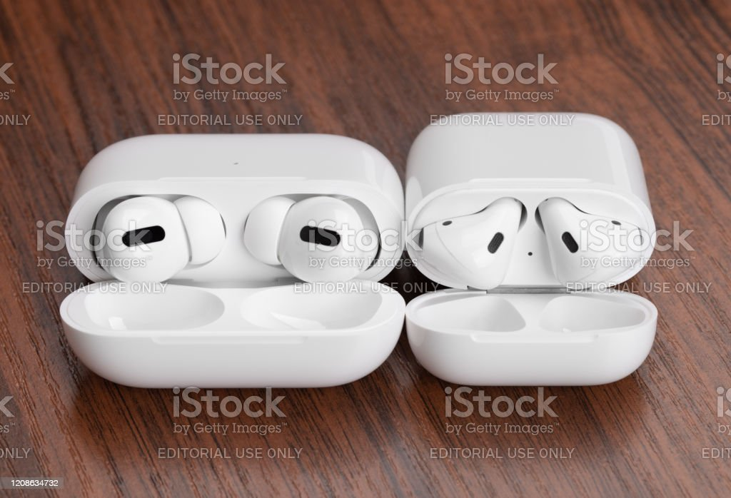 Apple Airpods Pro And Airpods On A Wooden Table Stock Photo