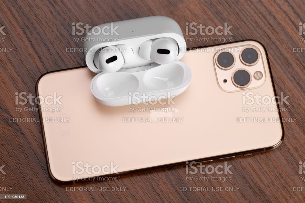 Apple Airpods Pro And Iphone 11 Pro On A Wooden Table Stock Photo