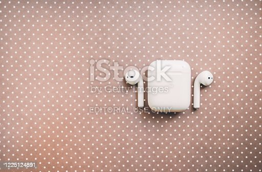 Apple AirPods wireless headphone with charging box on the color background. Use with Iphone, Ipad or Mac.