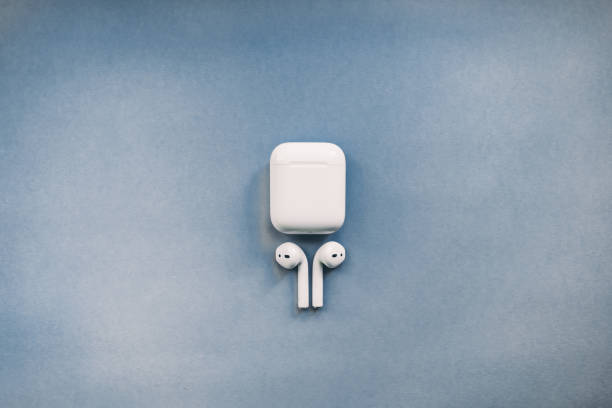 Apple AirPods wireless headphone with charging box on the color background. Apple AirPods wireless headphone with charging box on the color background. Use with Iphone, Ipad or Mac. plant pod stock pictures, royalty-free photos & images