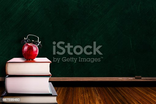 istock Apple Alarm Clock on Stack of Books and Chalkboard Background 667599460