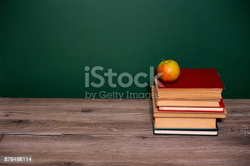 istock apple and book on wooden table 876498114