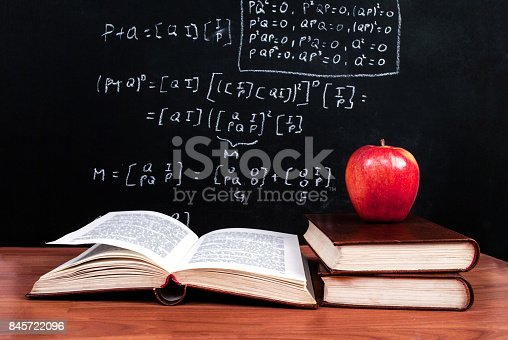 istock Apple and books on a wooden table and school blackboard with mathematical equations in the classroom 845722096