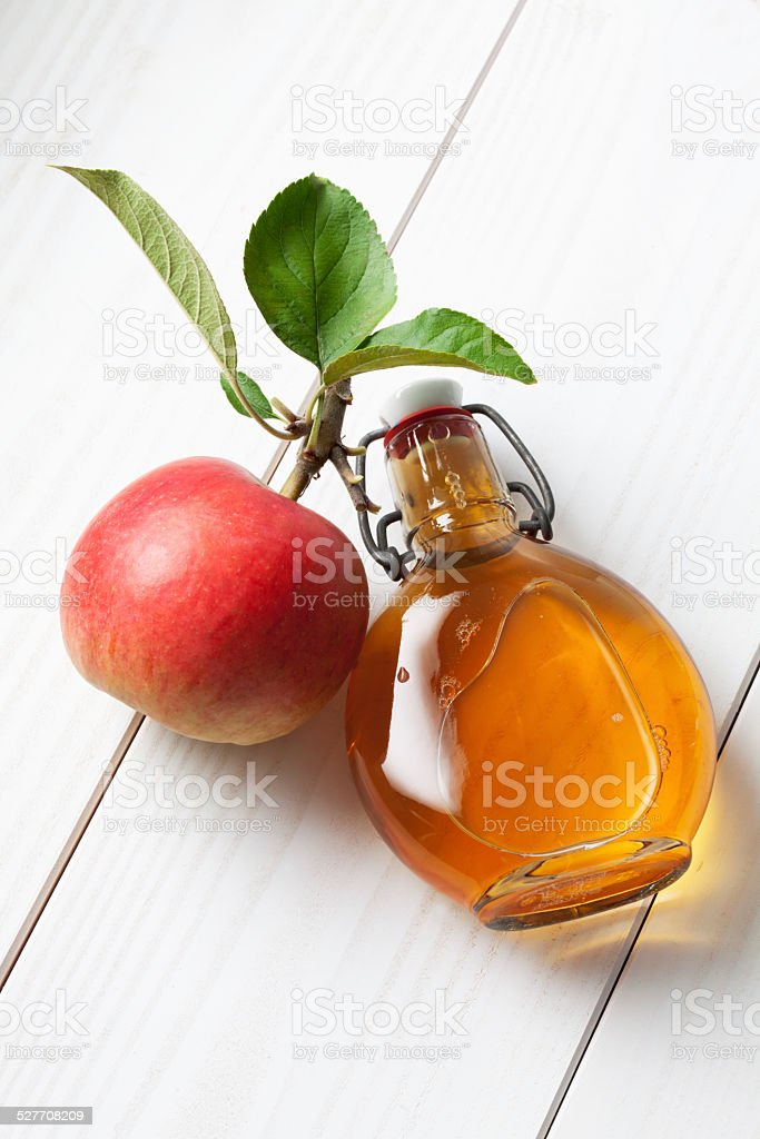 Apple and leaves glas bottle filled with apple cider vinegar stock photo