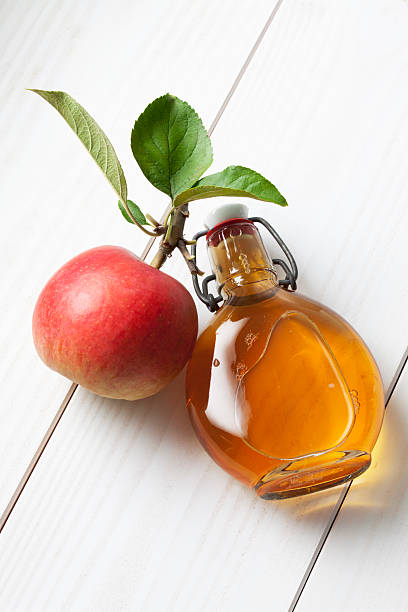 Apple and leaves glas bottle filled with apple cider vinegar stock photo