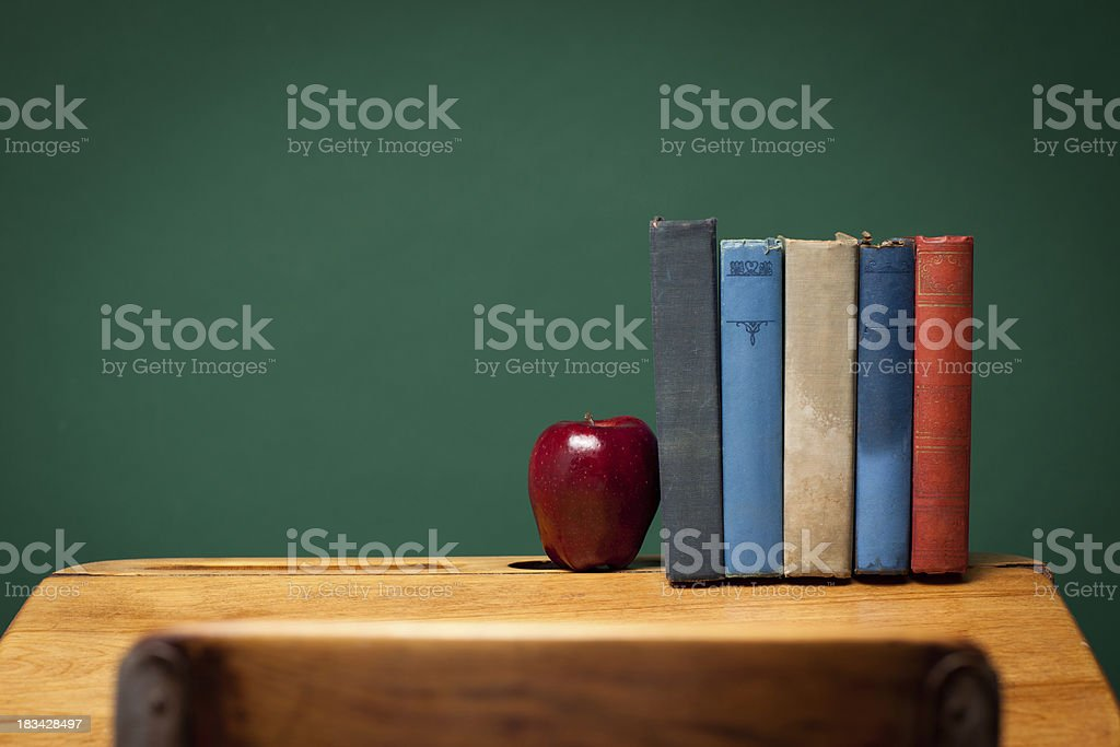 Apple and Old Books on School Desk by Chalkboard royalty-free stock photo