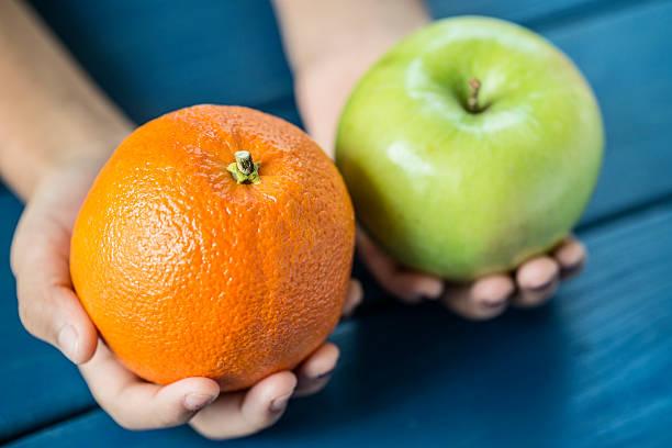 Comparação de laranja e de maçã - foto de acervo