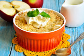 Apple and pear crumble in orange container.
