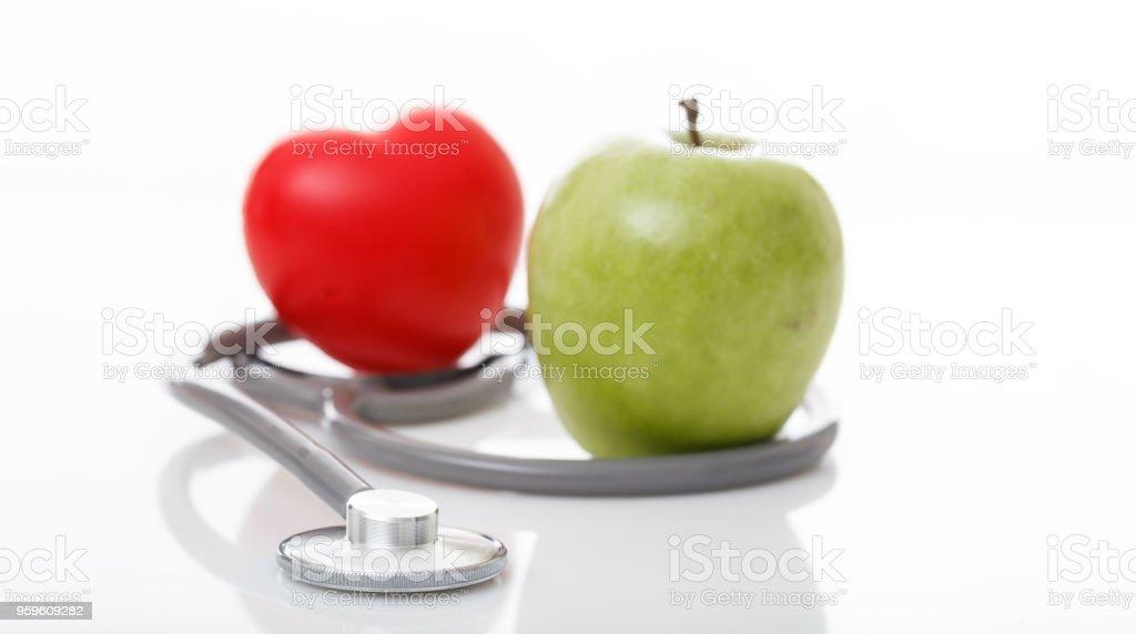 Apple y estetoscopio sobre fondo blanco - Foto de stock de Alimento libre de derechos