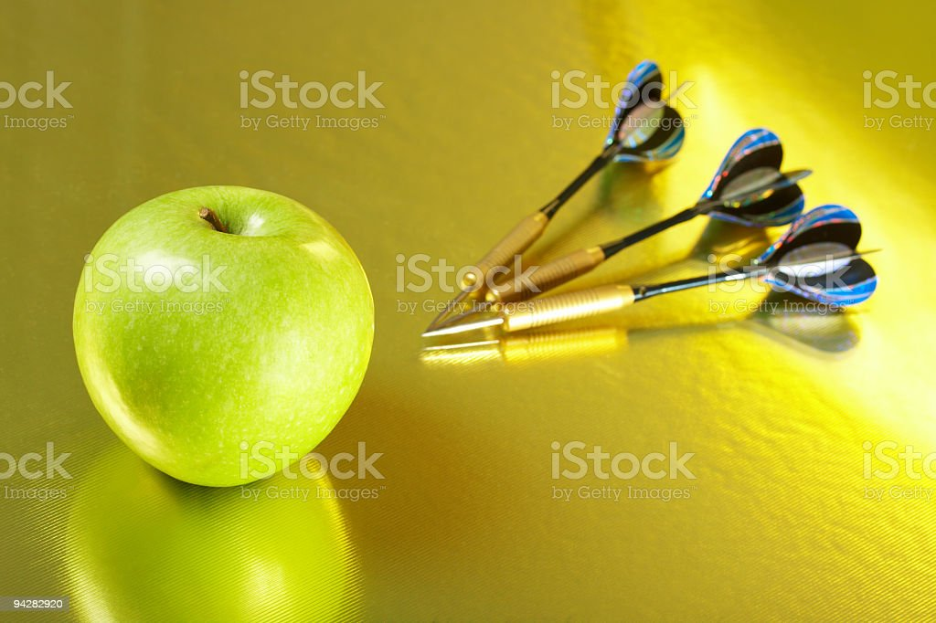 Apple and the darts laying on a golden background royalty-free stock photo