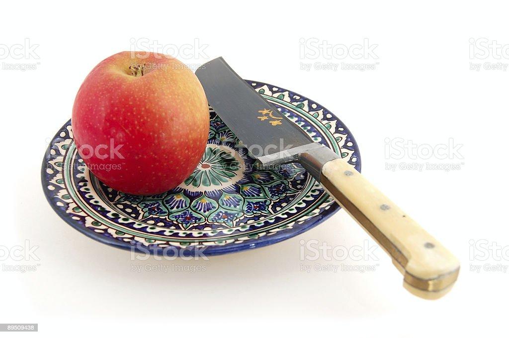 Apple et Uzbek Rishtan style couteau sur une plaque photo libre de droits