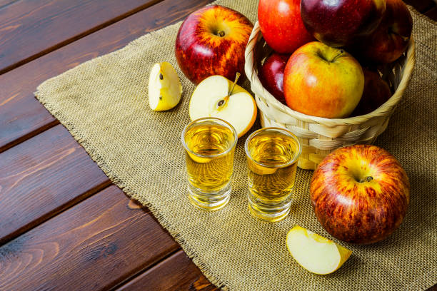 Apple brandy shots and red apples Apple brandy shots and red apples in the rustic wicker basket on wooden background calvados stock pictures, royalty-free photos & images