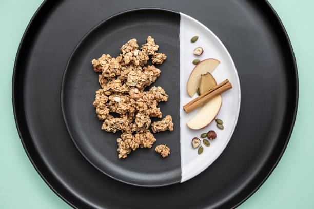 apple breakfast granola/muesli clusters on plate with scattered ingredients - anthony mcgovern stock photos and pictures