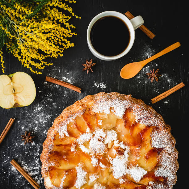 apple cake with coffee mug, apple fruit, cinnamon and mimosa flowers on table. flat lay, - mimosa cake foto e immagini stock