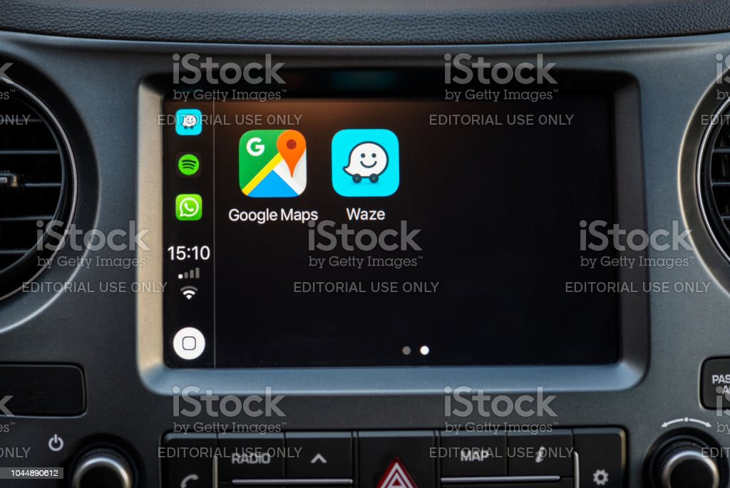 Apple Carplay screen in car dashboard displaying Google Maps and Waze apps stock photo