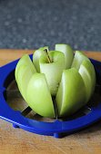 Using a blue metal Apple chopper to core and slice this green tasty apple. Focus is on the Apple core. Taken in June time in the UK.
