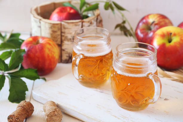 Apple Cider and red apples Two cups of Apple Cider and red apples in wooden  basket on light background hot apple cider stock pictures, royalty-free photos & images