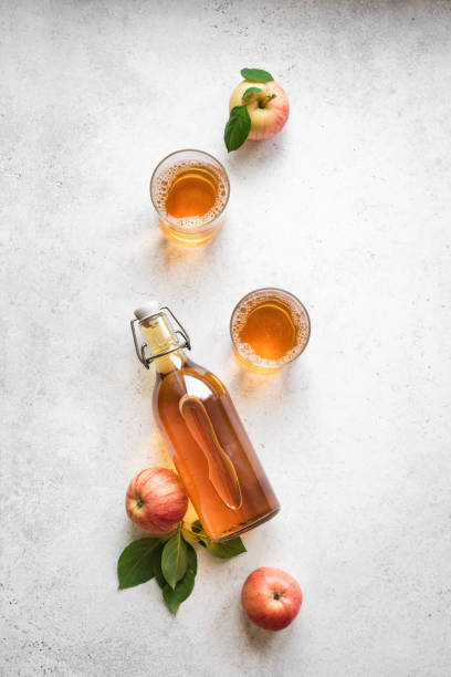 Apple cider drink Apple cider drink or fermented fruit drink and organic apples on white, top view, copy space. Healthy eating and lifestyle concept. vinegar stock pictures, royalty-free photos & images