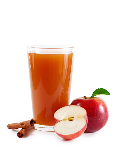 Apple cider glass decorated with fresh apples and cinnamon A glass of apple cider on white hot apple cider stock pictures, royalty-free photos & images