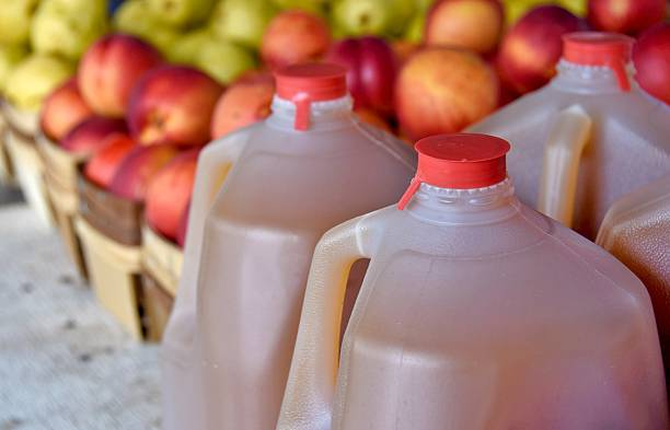 apple cider in gallon jugs autumn apple cider in plastic gallon jugs with apples at the market hot apple cider stock pictures, royalty-free photos & images