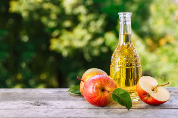 apple cider on table Apple cider, juice or vinegar in glass bottle on wooden table. Summer drink apple cider vinegar stock pictures, royalty-free photos & images
