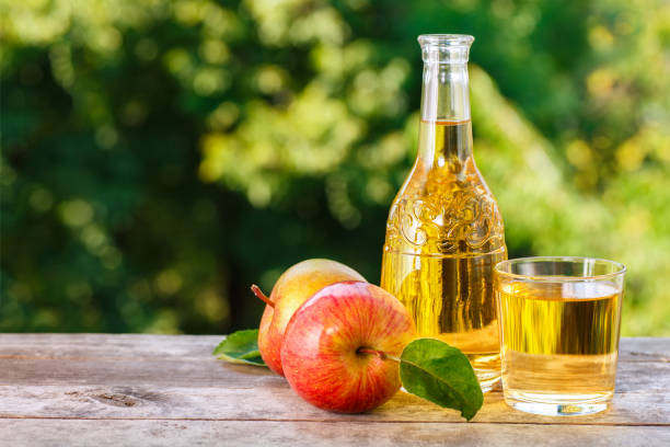 apple cider or juice apple cider or juice in glass with ripe fresh apples on wooden table with green natural background. Horizontal shot. Summer drink apple cider vinegar stock pictures, royalty-free photos & images