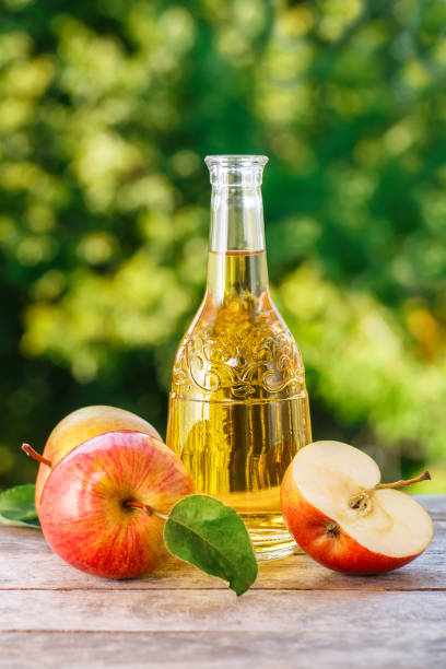 apple cider or vinegar apple cider, juice or vinegar in glass bottle and ripe fresh apples on wooden table with blurred natural background. Vertical shot. Summer drink apple cider vinegar stock pictures, royalty-free photos & images