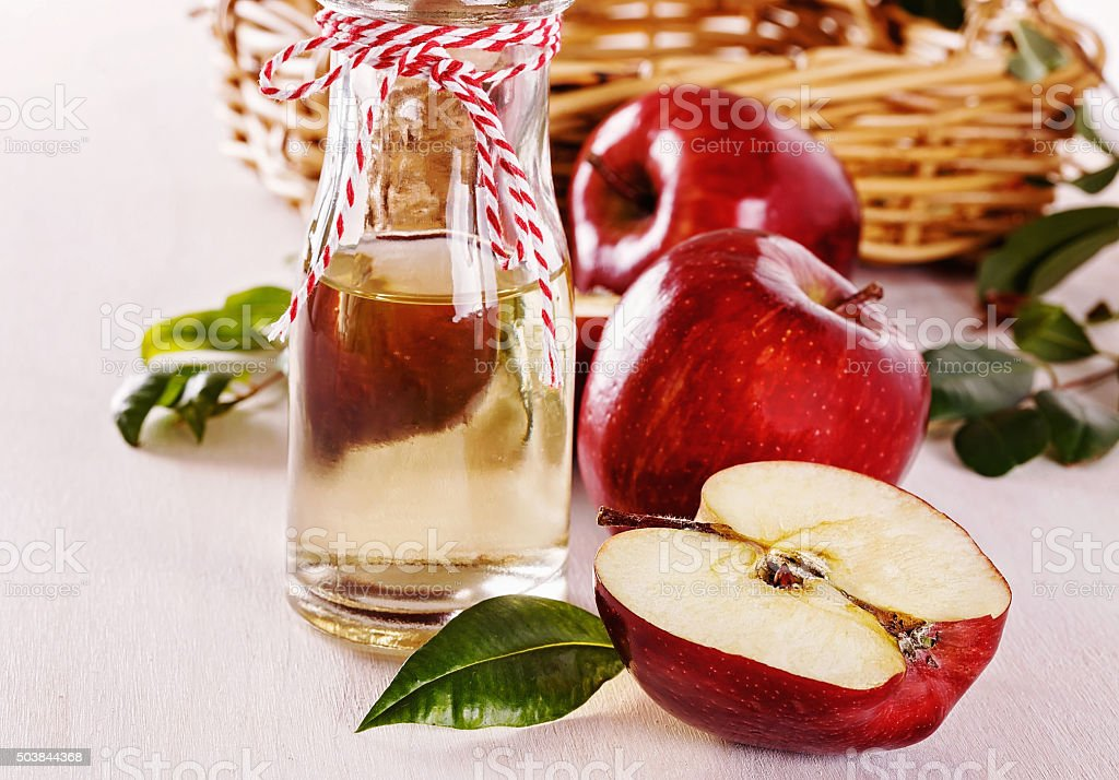 Apple cider vinegar and apples over white wooden background stock photo