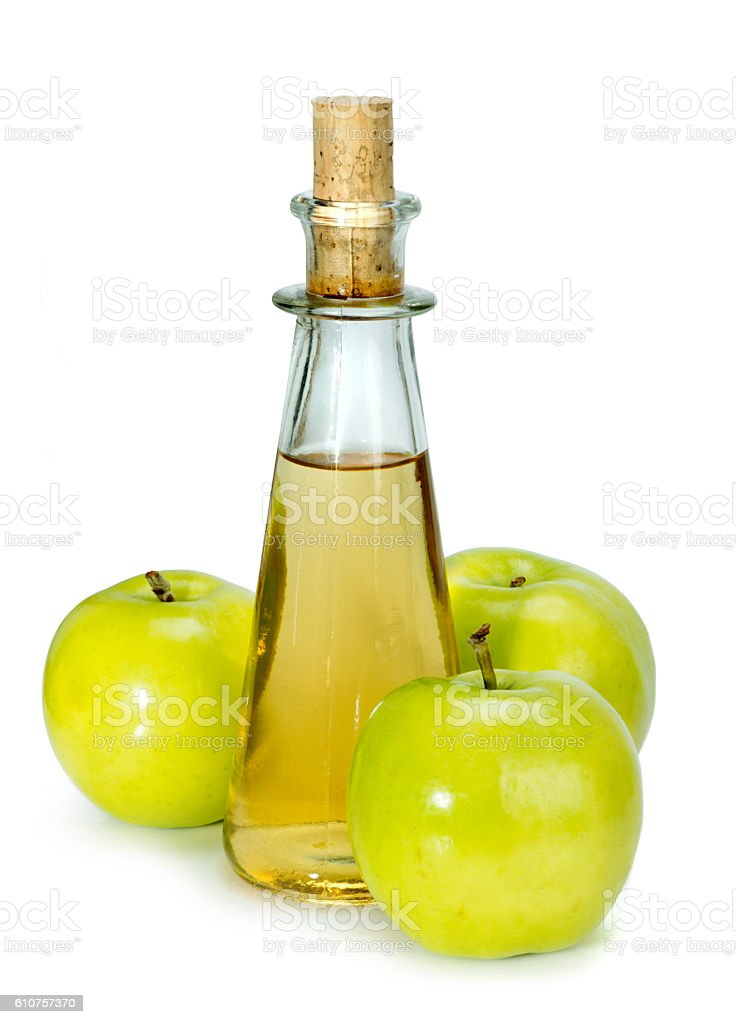 apple cider vinegar in a glass vessel and green apples stock photo