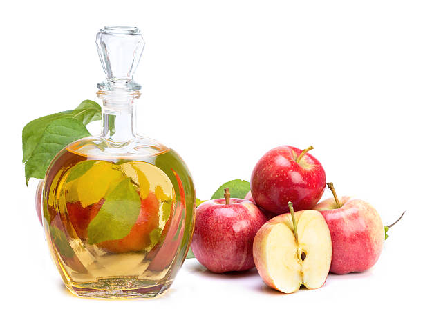 apple cider vinegar in a glass vessel and red apples stock photo