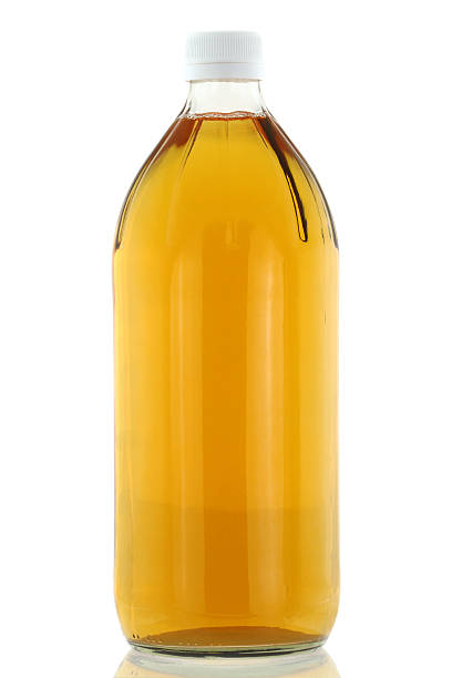 Apple Cider Vinegar isolated on white A bottle of filtered Apple Cider Vinegar isolated on white apple cider vinegar stock pictures, royalty-free photos & images