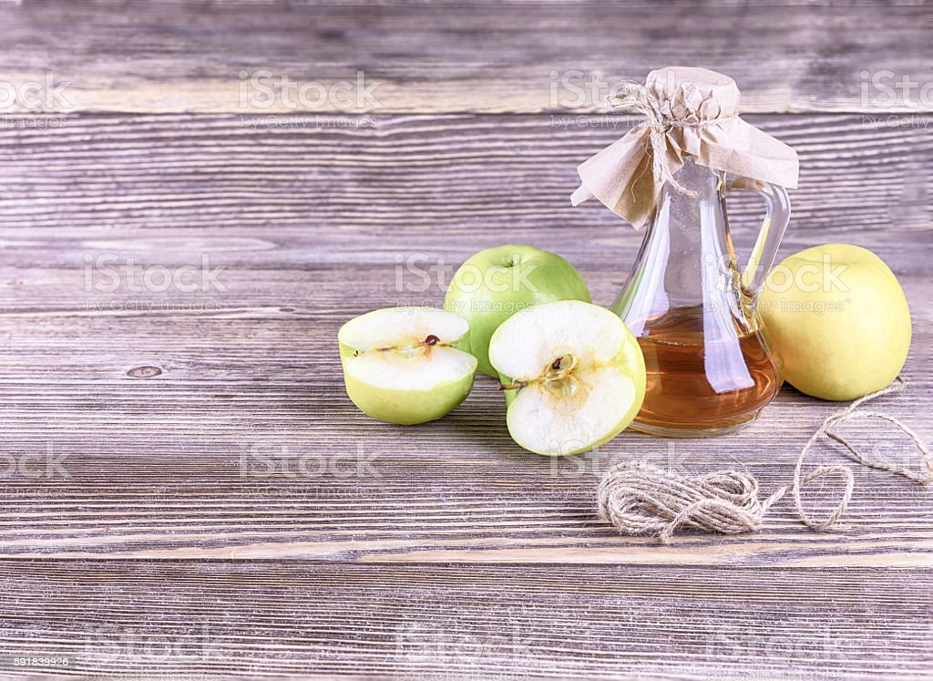 Apple cider vinegar on a background of wood stock photo
