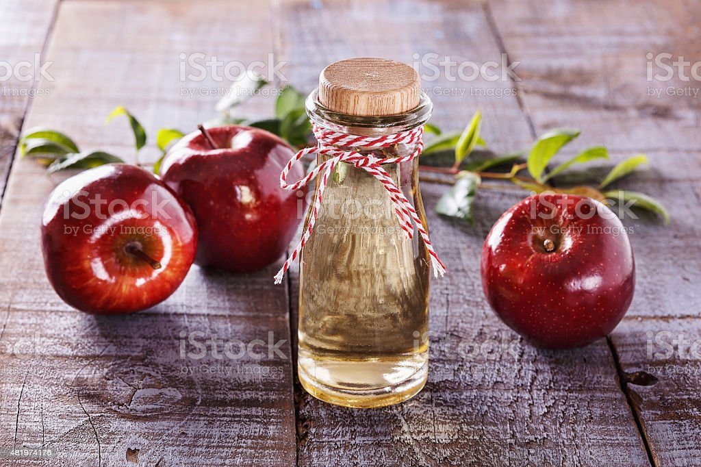 Apple cider vinegar over rustic wooden background stock photo