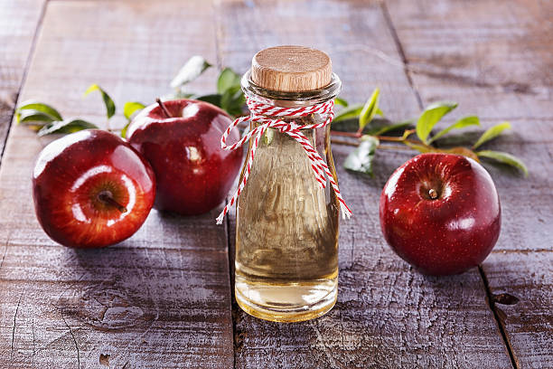 Apple cider vinegar over rustic wooden background Apple cider vinegar and red apples over rustic wooden background apple cider vinegar stock pictures, royalty-free photos & images