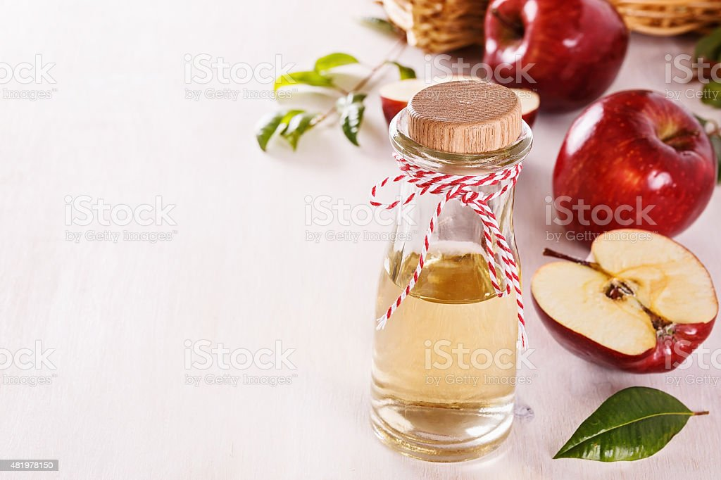 Apple cider vinegar over white wooden background stock photo