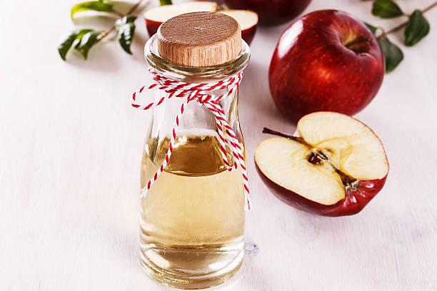 Apple cider vinegar over white wooden background Apple cider vinegar and red apples over white wooden background. Selective focus apple cider vinegar stock pictures, royalty-free photos & images
