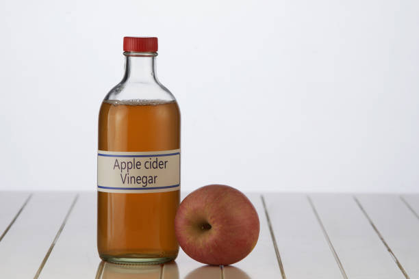 apple cider vinegar apple cide vinegar on white table top apple cider vinegar stock pictures, royalty-free photos & images