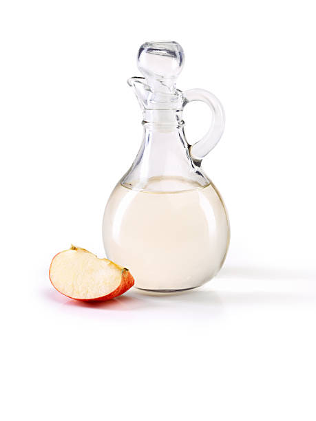 Apple cider vinegar- so many great health benefits Studio shot of a jug of apple cider vinegar with a slice of apple beside it apple cider vinegar stock pictures, royalty-free photos & images