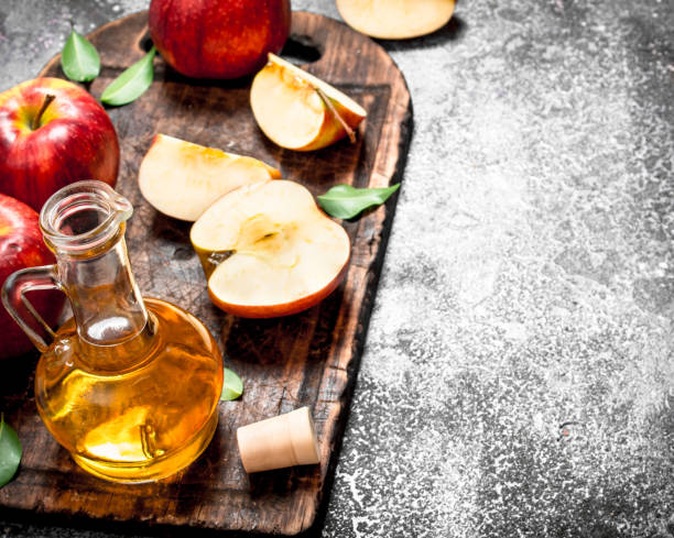 Apple cider vinegar with fresh apples on cutting Board. stock photo