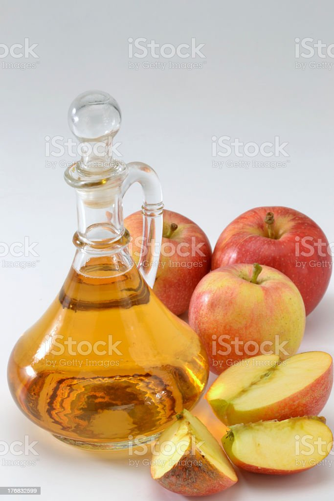 Apple cider vinegar with sliced and whole apples royalty-free stock photo