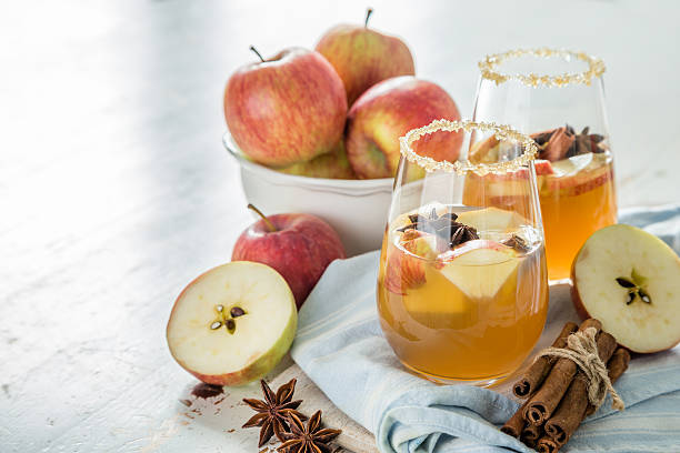 Apple cider with cinnamon and anise Apple cider with cinnamon and anise, wood background, copy space hot apple cider stock pictures, royalty-free photos & images