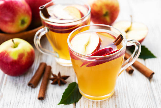 Apple cider  with cinnamon sticks Apple cider with cinnamon sticks on a old wooden table hot apple cider stock pictures, royalty-free photos & images