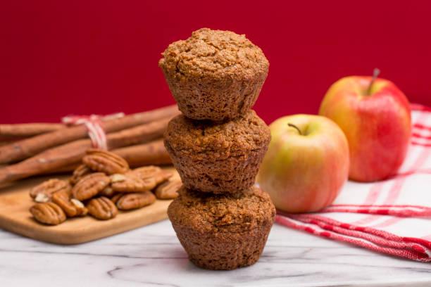 apfel-zimt pecan-muffins auf einen apfel rot unterlegt - cupcake türme stock-fotos und bilder