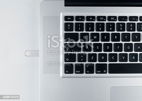 Istanbul, Turkey - July 9, 2013: Apple MacBook Pro laptop computer top view shown withmemory stick plugged in, on white.