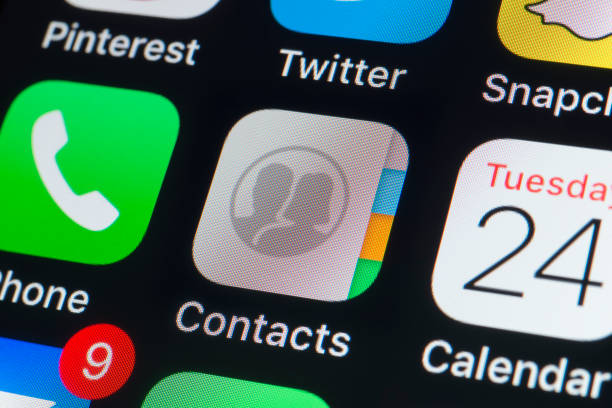 apple contacts, calendar,phone and other apps on iphone screen - address book stock photos and pictures