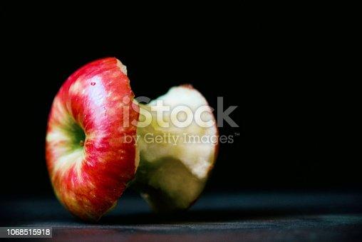 A half eaten apple on a wooden cutting board shot in studio.