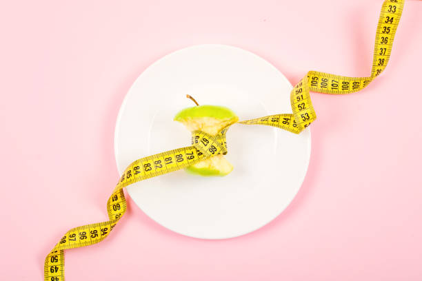 Apple core with measuring tape in place of the waist on a white plate on pink background. Diet, weigh loss, starvation, fitness concept. Apple core with measuring tape in place of the waist on a white plate on pink background. Diet, weigh loss, starvation, fitness concept. biological process stock pictures, royalty-free photos & images